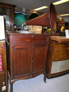 "This Auxetophone is in the 'Queen Anne' Style with a highly polished mahogany cabinet with panelled doors and cabriole legs. It has a triple-spring spiral-drive motor, 12"" turntable, speed indicator, tapering tone-arm with gooseneck, auxetophone soundbox, and a mahogany grained Flaxite horn. Part of the EMI Group Archive Trust collection"